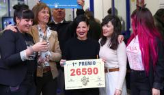 Un grupo de personas celebra el premio en Doña Manolita, que ha vendido el 26590.